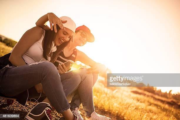 Urban Freundinnen sitzen auf skateboard und Spaß mit Mobiltelefon