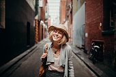 Smiling woman with casual clothes and a wig having fun in the street.