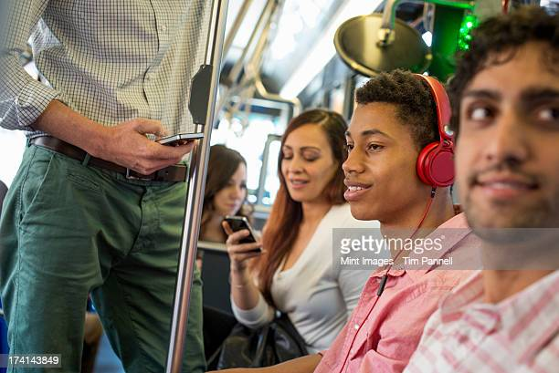 Urban Lifestyle. A group of people, men and women on a city bus, in New York city. A man with headphones on. A man and a woman checking their smart phones.