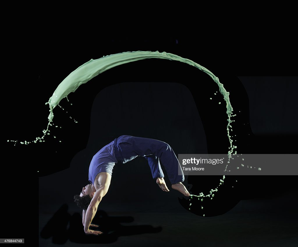 urban man doing back flip with green paint splash : Stock Photo
