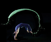 urban man doing back flip with green paint splash