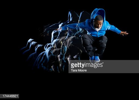 urban man jumping in air with multiple strobe