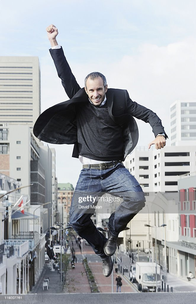 Urban man leaping with joy. : Stock Photo