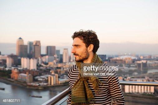 Urban man overlooks city.