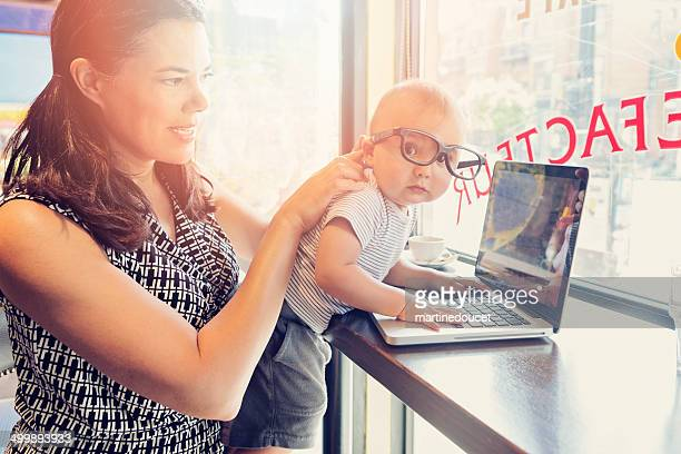 Urban mom balancing work and family in a public cafe.