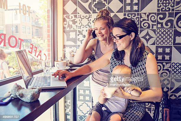 Urban mom balancing work and family with colleague in cafe.