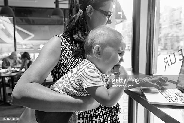 Urban mom with crying baby trying to work in cafe.