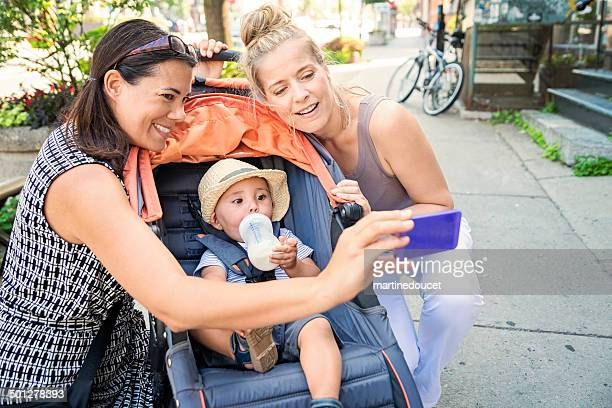 Urban mom with stroller doing selfie with baby and friend.