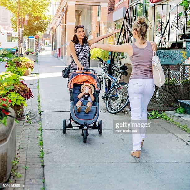 Urban maman avec une poussette réunion ami dans la rue.