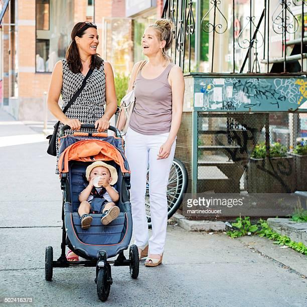 Urban mom with stroller meeting friend on street.