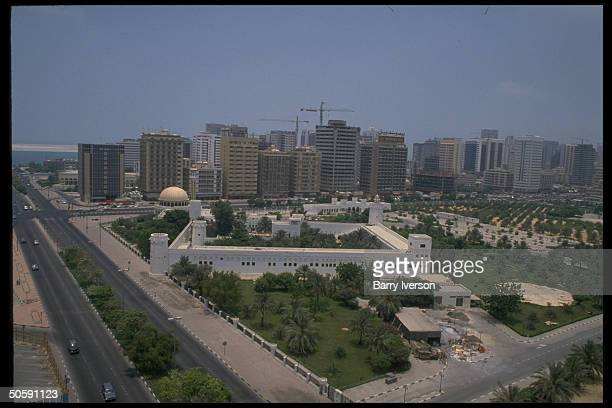 Urban panorama featuring AlHosn Palace aka White Fort Abu Dhabi's oldest w mosque modern office apartment bldgs looming beyond