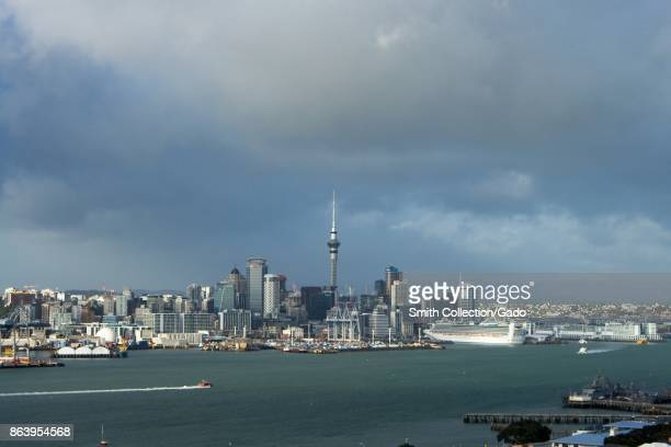 Urban skyline of Auckland New Zealand including the iconic Sky Tower from across Auckland Harbor on Mount Victoria on an overcast day with cruise...