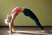 Portrait of sporty beautiful blond young woman in sportswear working out indoors, doing backbend, Bridge Pose, Urdhva Dhanurasana (Upward Bow), Chakrasana (Wheel) posture on orange mat, full length