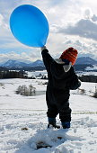 kleiner Junge im Schneeanzug mit Mütze und Schal hält einen blauen Ballon in die Luft. Winterlandschaft mit Wolkenhimmel im Hintergrund. Gegenlichtaufnahme.