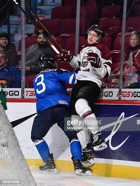 Urho Vaakanainen of Team Finland checks Erlends Klavins of Team Latvia into the boards during the 2017 IIHF World Junior Championship relegation game...