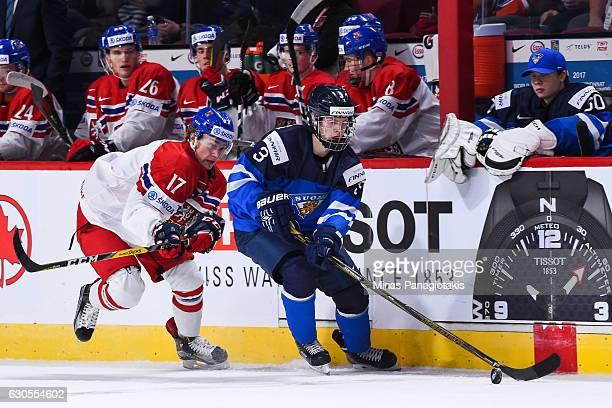 Urho Vaakanainen of Team Finland skates the puck against Lukas Jasek of Team Czech Republic during the IIHF World Junior Championship preliminary...