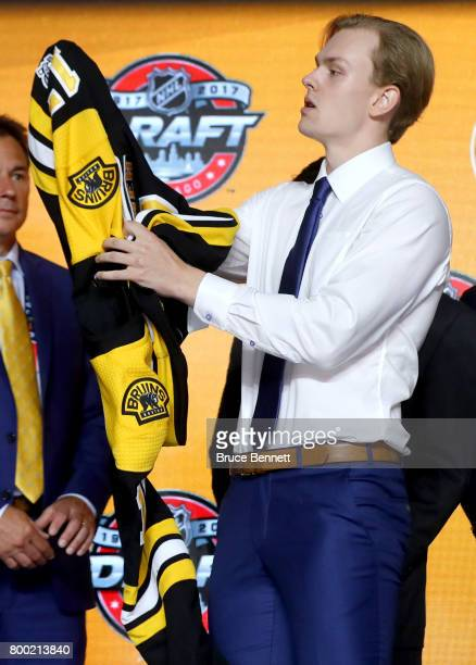 Urho Vaakanainen puts on the Boston Bruins jersey after being selected 18th overall during the 2017 NHL Draft at the United Center on June 23 2017 in...
