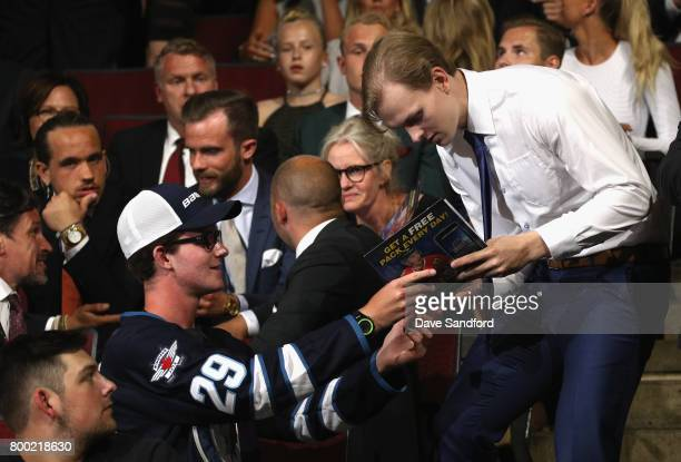 Urho Vaakanainen signs an autograph after being selected 18th overall by the Boston Bruins during Round One of the 2017 NHL Draft at United Center on...
