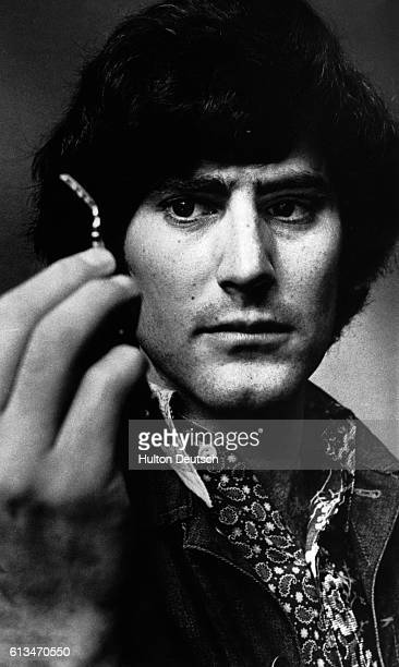 Uri Geller the psychic performer holds up a spoon which he claims he bent using only the power of his mind ca 1978