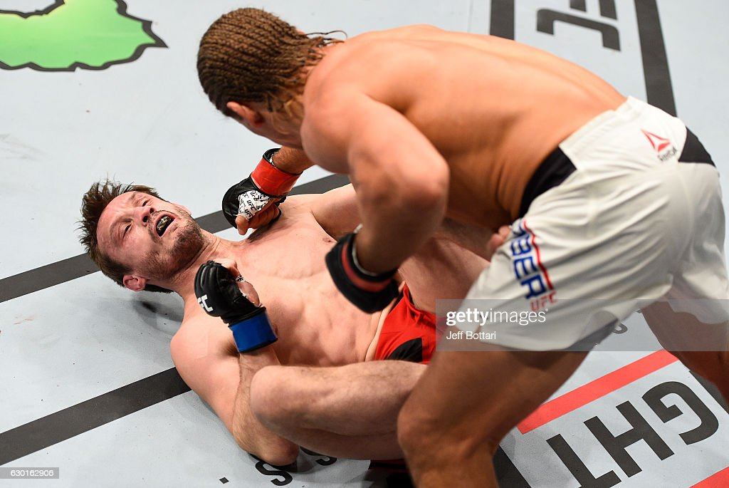 Urijah Faber punches Brad Pickett of England in their bantamweight bout during the UFC Fight Night event inside the Golden 1 Center Arena on December 17, 2016 in Sacramento, California.
