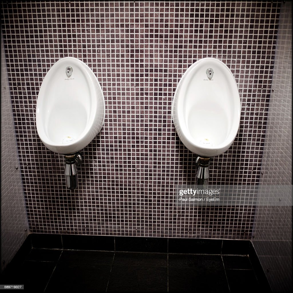 Urinals Mounted On Tile Wall In Public Restroom