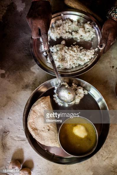 Urmila Devi prepares a plate of roti rice and lentils with unripe mango for a meal in Auar Village in the Pratapgarh district of Uttar Pradesh India...