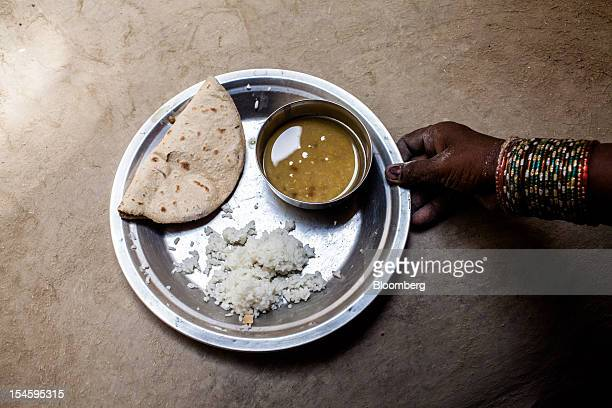 Urmila Devi puts a plate of roti rice and lentils on the ground for a photograph in Auar Village in the Pratapgarh district of Uttar Pradesh India on...