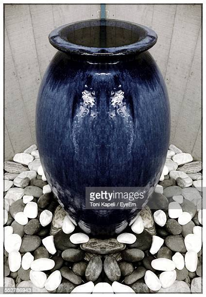 Urn Amidst Pebbles In Garden