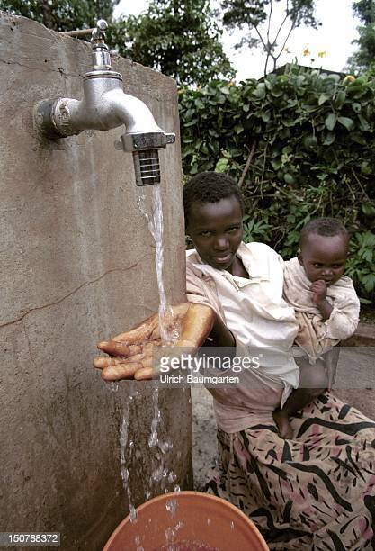 Uroki 'SharkDistrict Waterproject' at Arusha Our picture shows a young woman with baby sitting at the well and daming up water in her hand