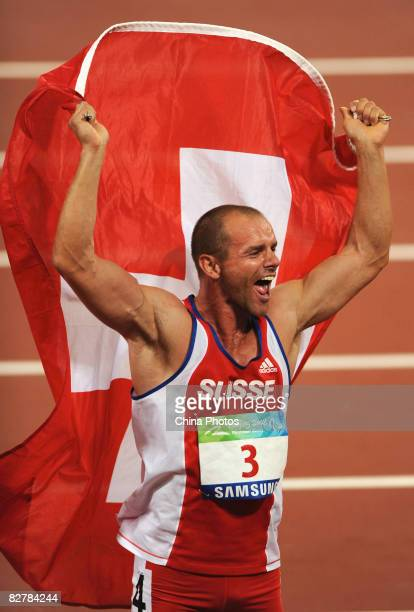 Urs Kolly of Switzerland celebrates with a flag after the Men's Pentathlon P44 Athletics event at the National Stadium during day five of the 2008...