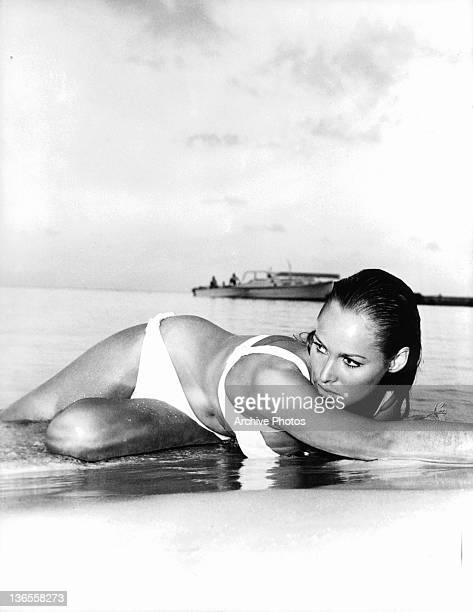 Ursula Andress lying on the shore of a beach in a seductive manner in a scene from the film 'James Bond Dr No' 1962