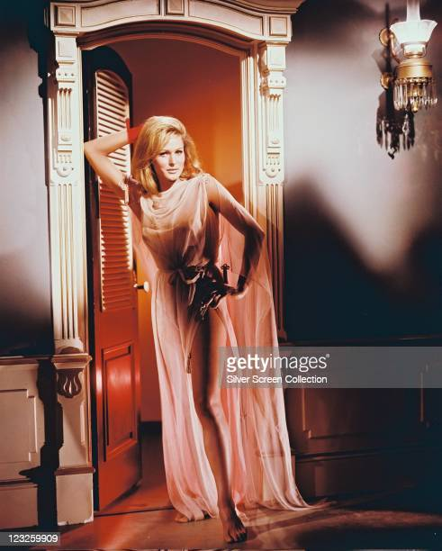 Ursula Andress Swiss actress long pink sheer fabric nightdress with a split skirt exposing her left leg as she poses in a doorway her right elbow...