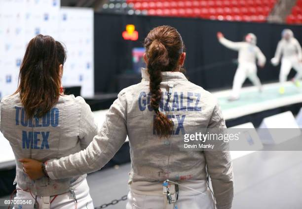 Ursula Gonzalez Garate of Mexico and teammate Julieta Toledo watch a teammate fence during the gold medal match in the Team Women's Sabre event on...