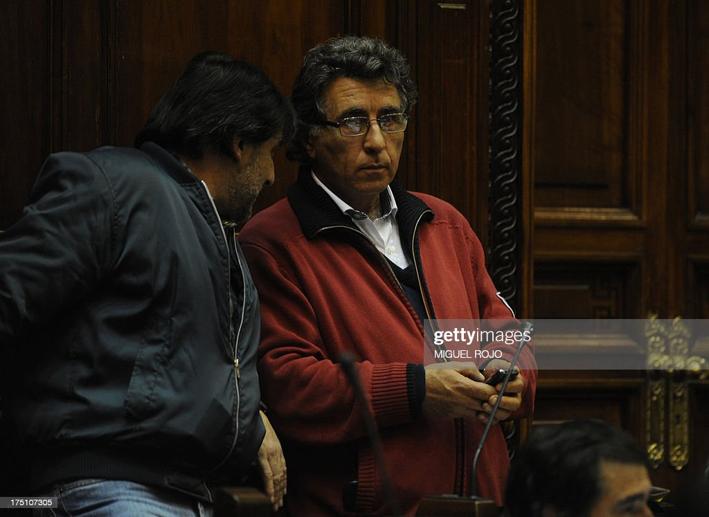 Uruguayan deputy Dario Perez (R), of the ruling leftist coalition party Frente Amplio, listens to a colleague during the parliament session debating the bill legalizing marijuana, in Montevideo, on July 31, 2013. Uruguay's lower house voted --50 out of 96-- the controversial bill which for the first time would put a government in charge of production and distribution of legal marijuana. The bill, unveiled in June 2012 as part of a series of measures to combat rising violence, will now head to the Senate for final passage.