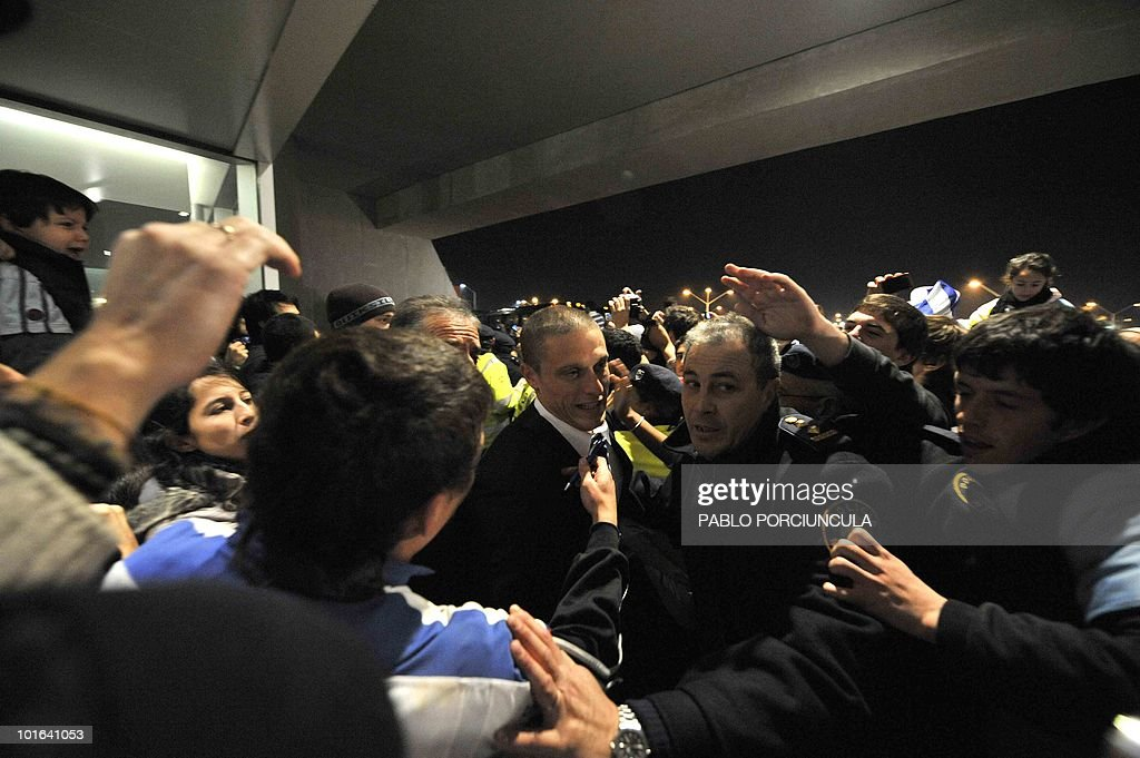 Uruguayan footballer Diego Perez (C) is greeted by supporters as he arrives at Carrasco airport in Montevideo on June 5, 2010. The Uruguayan national football team departed to South Africa to participate in the FIFA World Cup South Africa 2010. AFP PHOTO/Pablo PORCIUNCULA