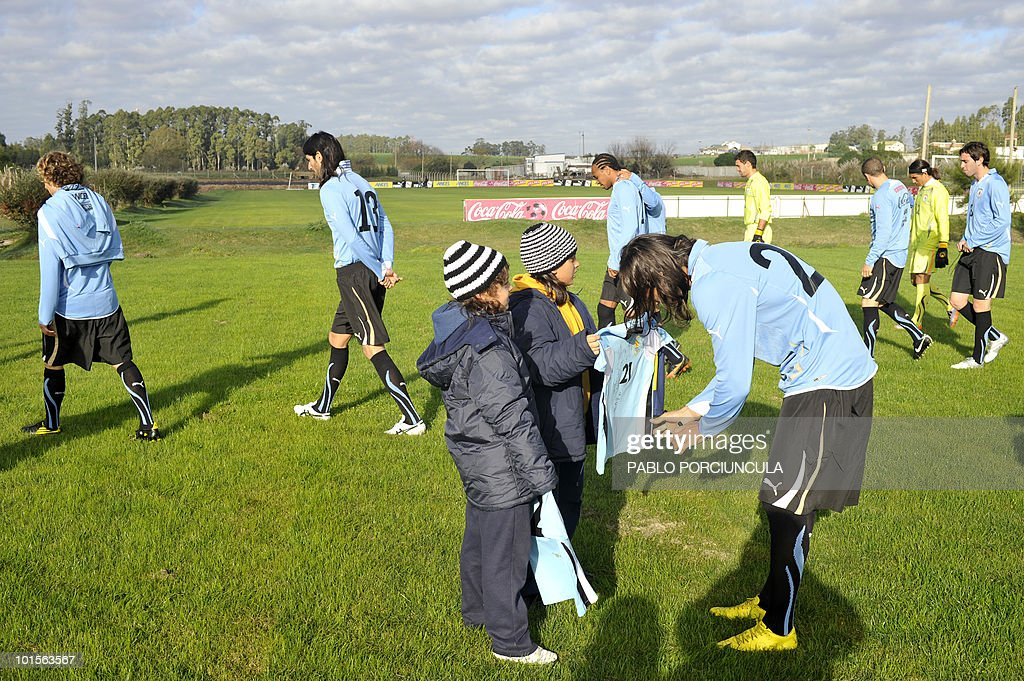 Uruguayan footballer Martin Caceres signs autographs before a training session on June 2, 2010 in Canelones, Uruguay. AFP PHOTO/Pablo PORCIUNCULA