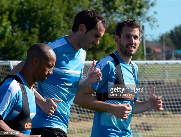 Uruguayan footballers Diego Godin Carlos Sanchez Christian Stuani jog during a training session ahead of their FIFA World Cup South American...