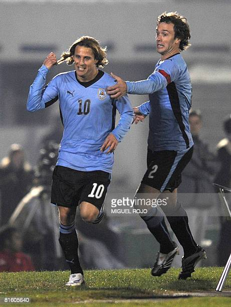 Uruguayan forward Diego Forlan celebrates after scoring next to his teammate Diego Lugano during the match against Peru for the FIFA World Cup South...