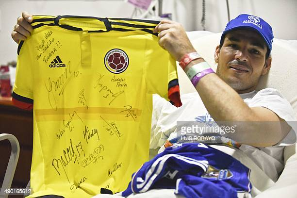 Uruguayan goalkeeper Alexis Viera of Colombia's Depor FC team shows a Colombian national team jersey signed by players during an interview with AFP...