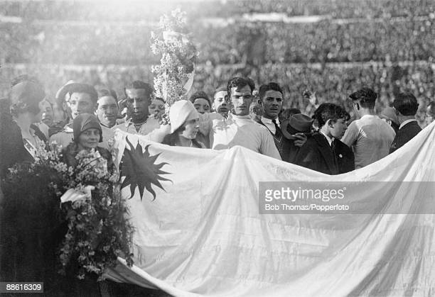 Uruguayan goalkeeper Enrique Ballesteros holding a bouquet of flowers as the team fans and officials line up behind the national flag during the...