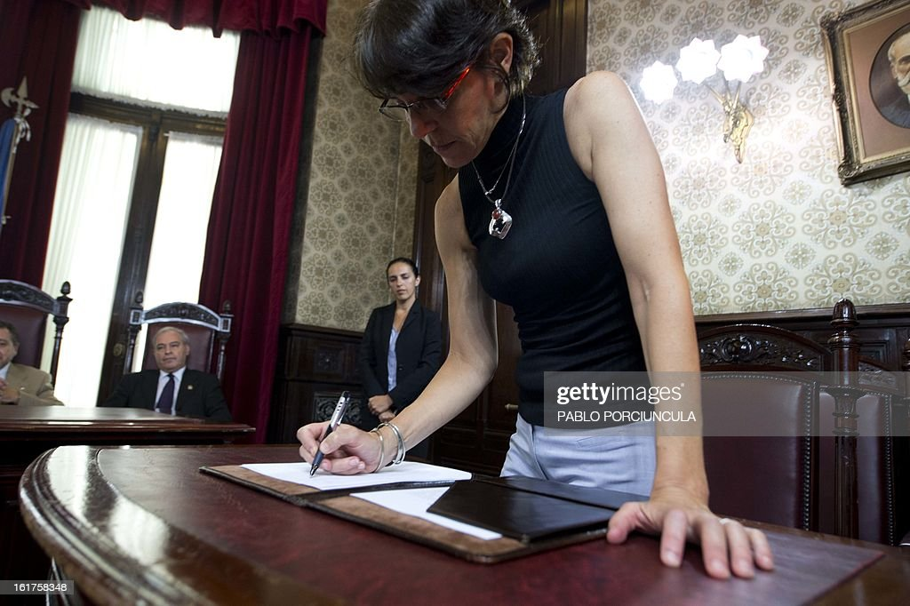 Uruguayan judge Mariana Mota signs for her new charge at the Supreme Court of Justice on February 15, 2013. Members of Human Rights organizations occupied the building in support of jugde Mariana Mota, who was transfered from her penal office, where she worked on about 50 cases of human rights abuses during the 1973-1985 dictatorship in Uruguay, to a civilian court . AFP PHOTO/Pablo PORCIUNCULA
