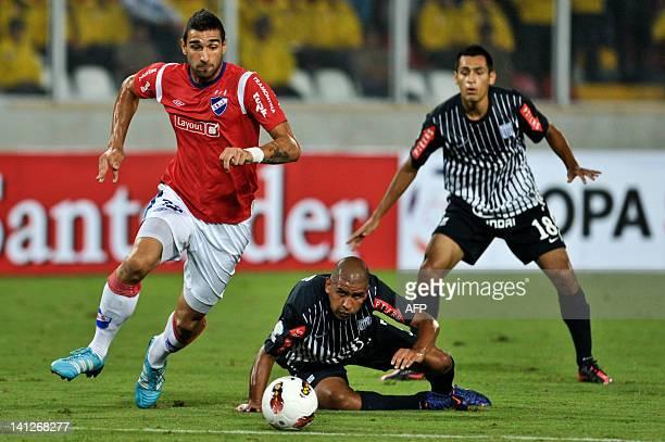 Uruguayan Nacional's Joaquin Boghossian vies for the ball with Peruvian Alianza Lima's midfielder Edgar Gonzalez during their 2012 Libertadores Cup...