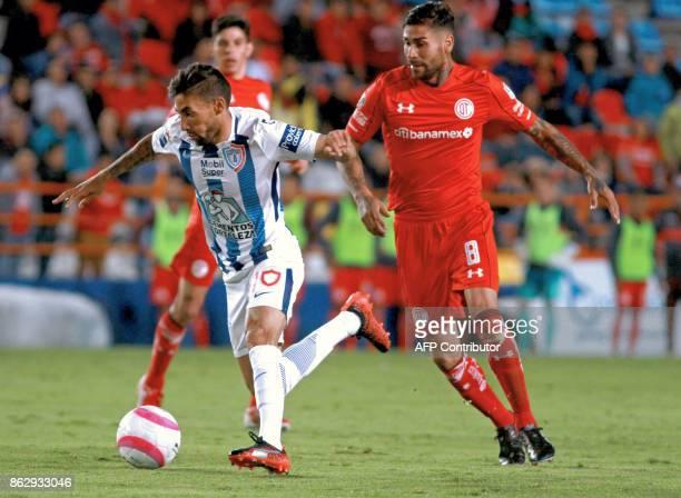 Uruguayan player Jonathan Urretaviscaya of Pachuca vies for the ball with Jesus Mendez of Toluca during their Mexican Apertura tournament football...