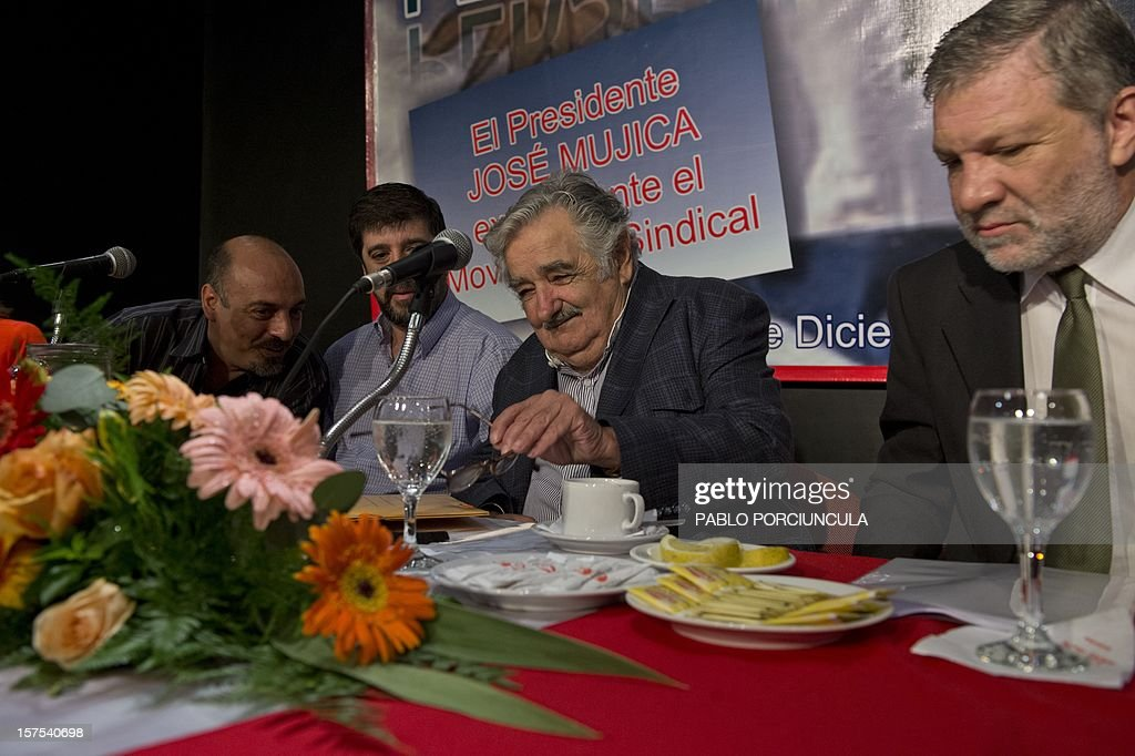 Uruguayan President Jose Mujica (C) prepares himself to speak, next to Uruguayan PIT-CNT (Union Federation) coordinators Marcelo Abdala (L), Fernando Pereira (2nd-L) and his Industry minister Roberto Kreimerman, during a working breakfast at the headquarters of the PIT-CNT Uruguayan labor union federation in Montevideo on December 4, 2012. AFP PHOTO/Pablo PORCIUNCULA