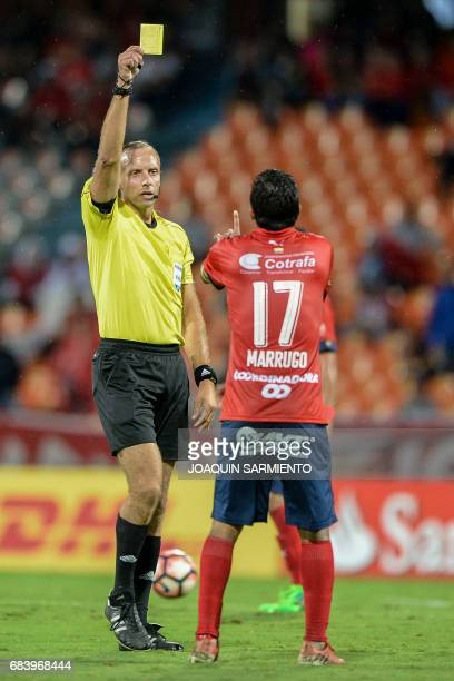 Uruguayan referee Daniel Fedorczuk shows the yellow card to Colombia's Independiente Medellin midfielder Christian Marrugo during their 2017 Copa...