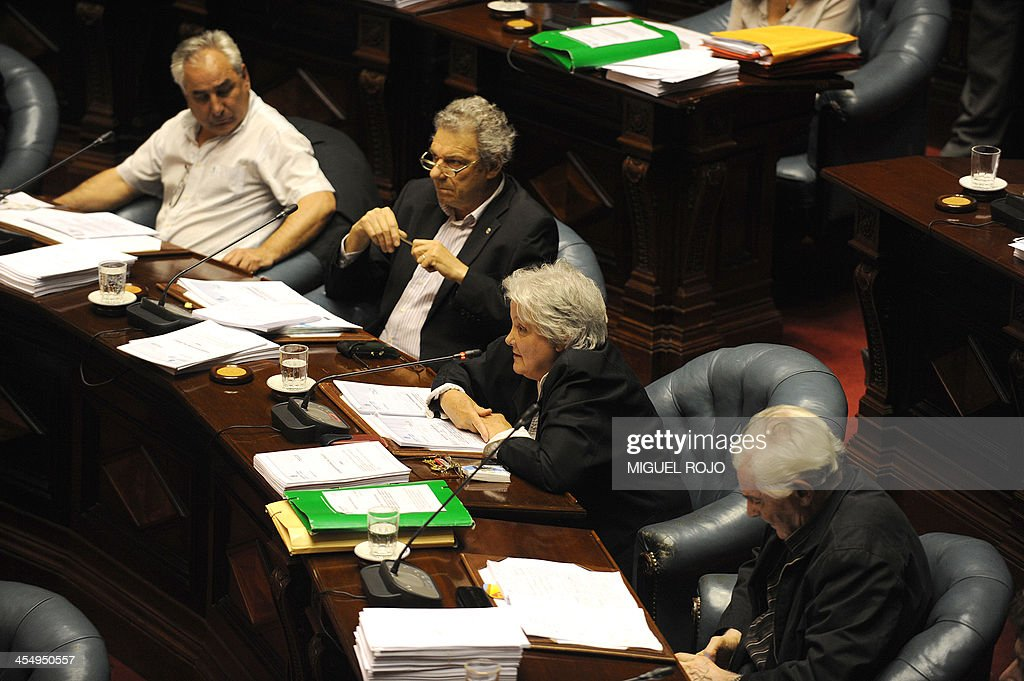 Uruguayan Senator Lucia Topolansky (C) votes to approve a law legalizing marijuana in the Legislative Palace in Montevideo, on December 10, 2013. The initiative launched by 78-year-old Uruguayan President Jose Mujica, a former revolutionary leader, will enable the production, distribution and sale of cannabis, self-cultivation and consumer clubs, all under state control. AFP PHOTO/ Miguel ROJO