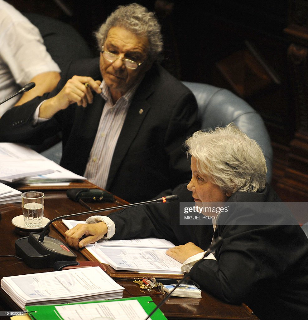 Uruguayan Senator Lucia Topolansky (R) votes to approve a law legalizing marijuana in the Legislative Palace in Montevideo, on December 10, 2013. The initiative launched by 78-year-old Uruguayan President Jose Mujica, a former revolutionary leader, will enable the production, distribution and sale of cannabis, self-cultivation and consumer clubs, all under state control. AFP PHOTO/ Miguel ROJO