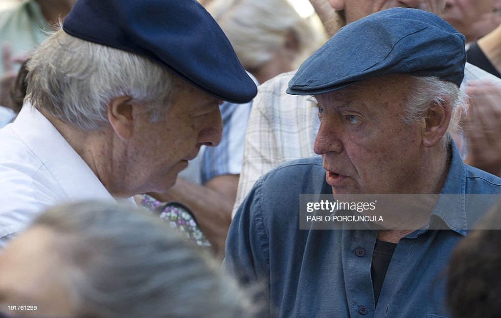 Uruguayan writer Eduardo Galeano (R) and songwriter Daniel Viglietti take part in a demonstration in support of judge Mariana Mota in front of the Justice Supreme Court headquaters in Montevideo on February 15, 2013. Members of Human Rights organizations occupied the building in support of jugde Mariana Mota, who was transferred from her penal office, where she worked on about 50 cases of human rights abuses during the 1973-1985 dictatorship in Uruguay, to a civilian court . AFP PHOTO/Pablo PORCIUNCULA