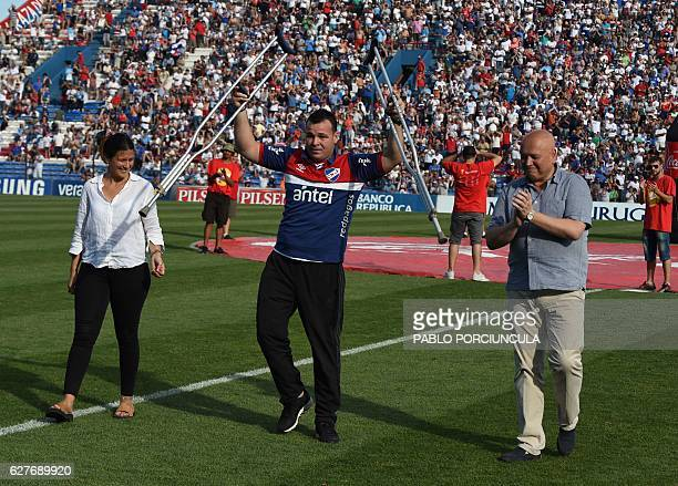 UruguayanColombian former goalkeeper Alexis Viera waves holding his crutches during an homage before the start of the Nacional vs Juventud Las...