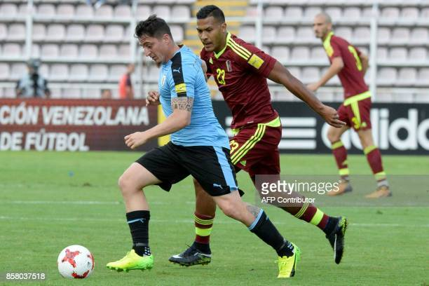 Uruguay's Cristian Rodriguez is marked by Venezuela's Salomon Rondon during their 2018 World Cup qualifier football match in San Cristobal Venezuela...